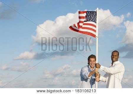 Multi-ethnic men holding American flag
