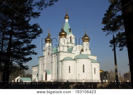 White Orthodox Church with golden domes and crosses.