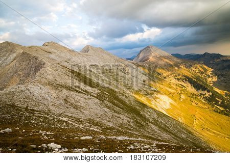 View across the peaks of the Pirin Mountains in Bulagaria with Vihren Kutelo and Banski Suhodol joined by the Koncheto Saddle under a stormy cloudy sky with a shaft of sunlight illuminating the range