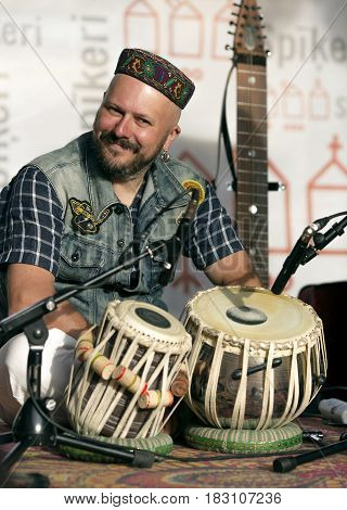 LATVIA, RIGA, JUNE, 10, 2016 - Musician in oriental headdress with tabla drums prepares to perform in Riga, Latvia.The tabla is a popular Indian percussion instrument used in the classical, popular and religious music of the Indian subcontinent.
