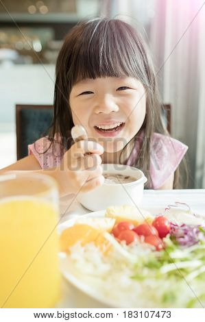 Cute Asian girl eating breakfast and smiling happily.