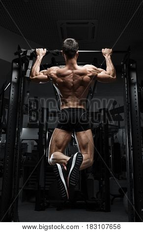 Athlete muscular fitness male model pulling up on horizontal bar in a gym