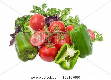 Branch with ripe red tomatoes several green bell peppers bisected one tomato and bisected one pepper and bundle of the greenery on a light background
