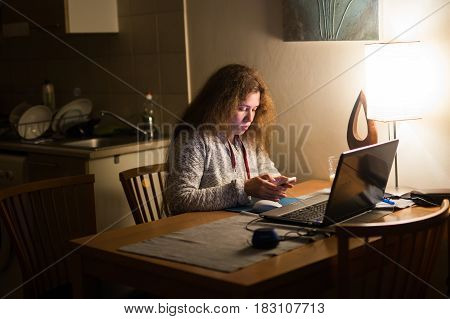 young woman late at night texting using mobile phone sleepy and tired in internet communication overuse concept and smart phone addiction.