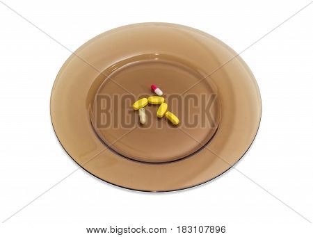 Several yellow tablets of the multivitamins and different dietary supplements in the form of capsules on the big dark glass dish on a light background