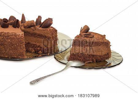 Partly sliced round layered chocolate cake decorated with chocolate chips and sprinkled with cocoa powder on the dark glass dish and slice cake on saucer with spoon on a light background