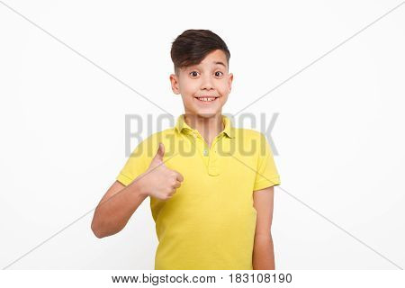 Little boy wearing yellow t-shirt posing on white background and showing thumb up.