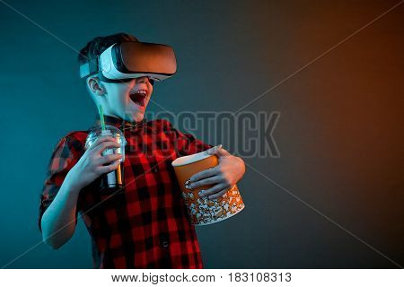 Happy little boy in VR glasses holding popcorn and cola on plain background.