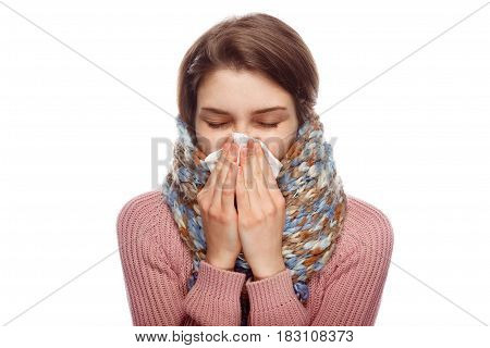 Young woman cuddling in scarf and sneezing in tissue isolated on white background.