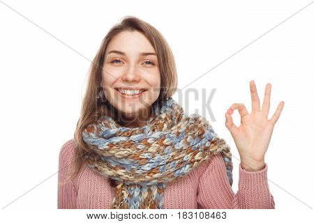 Smiling girl in scarf showing OK gesture on white background.