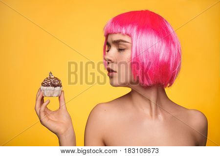 Young female model wearing pink wig and holding small delicious cupcake on yellow background.