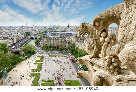 Top view of Paris from the tower of the Cathedral Notre-Dame de Paris with the gargoyles on the foreground against of sky with clouds
