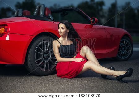Cute Young Brunette Woman Sitting On The Ground Near The Wheel Of Luxury Red Cabriolet Car.