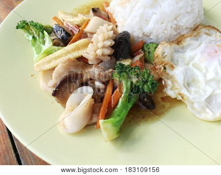 Vegetable Stir Fry In A Plate On Old Wooden Background With Rice And Fried Egg. Thai Style Food.
