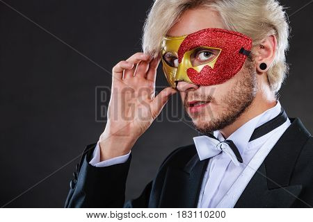 Young Man In Carnival Mask On Dark