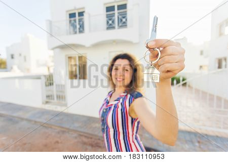 Concept of housewarming, real estate, property and moving - New home owner with key.