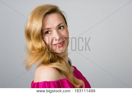 Portrait of a 39 year old woman in a pink dress