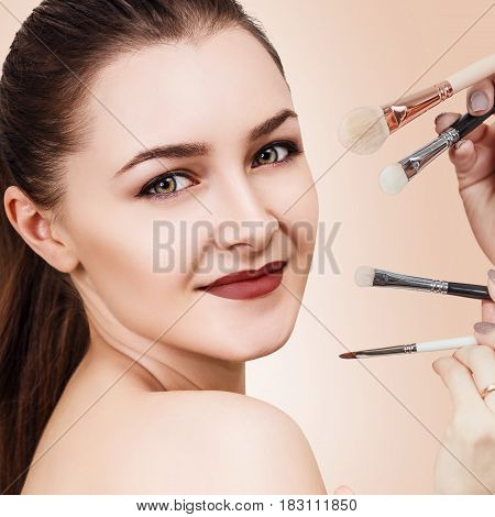 Hands with cosmetics brushes doing make-up to young woman, over beige background