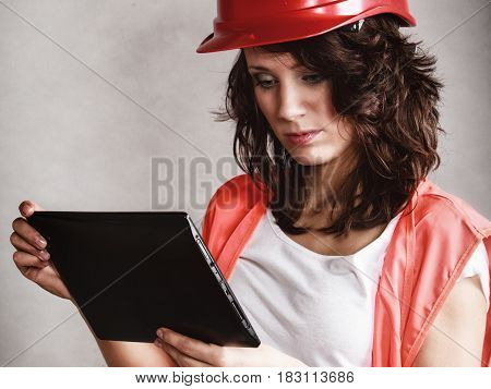 Sex equality and feminism. Sexy girl in workwear safety helmet and orange vest using tablet touchpad ipad on gray. Young attractive woman as construction worker. Technology.