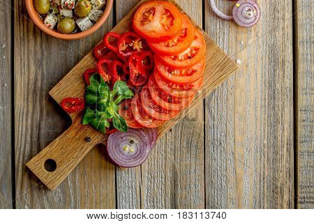 Ingredients for cooking salad in ceramic ware on a wooden table