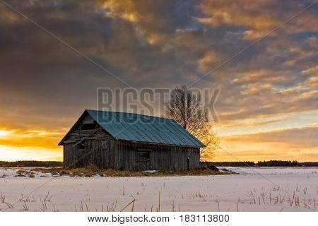 An old barn house against the springtime sunset in the Northern Finland. The sun starts to melt the snow but it's still quite cold.