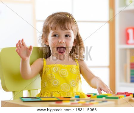 Little girl kid playing with logical toys in daycare center. Child sorting and arranging colors and forms.