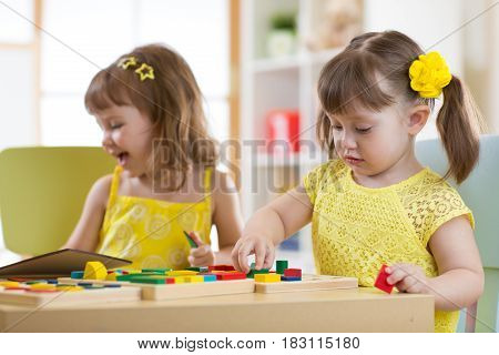 Preschool kids playing with educational sorter toys in classroom, kindergarten or home