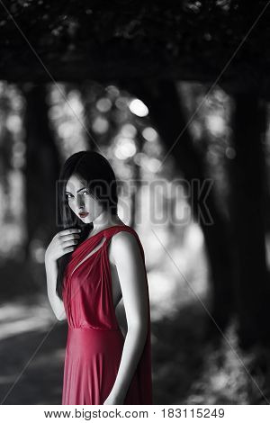 Sexy fashion model walking in a fantastical forest by footpath.Mystical portrait of sensual seductive woman with naked back in luxury long red dress posing against bokeh trees background. Multi-racial Asian Caucasian girl. Fashionable toning. Creative com