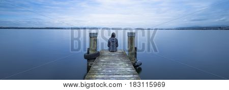Self reflection. One woman sits on a wooden pier. Cloudy above the lake. Long exposure.