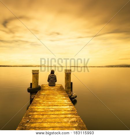 Self reflection in magical world of fantasy. One woman sits on a wooden pier. Cloudy above the lake. Long exposure.