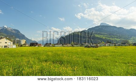 Panorama of the town Brunnen. Traditional Alpine meadows with luscious bright grass. Tractor fertilizes the field. Travel to Europe.