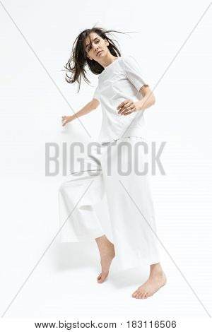 Attractive barefoot girl with windy hair is posing in the studio on the white background. She wears a white T-shirt and pants. Woman holds right hand on the wall and right leg on the toe. Vertical.