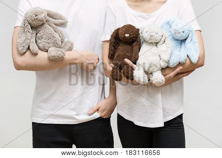 Man and woman in white T-shirts and black pants in the studio on the light background. They are holding plush multicolored rabbit toys. Closeup. Horizontal.