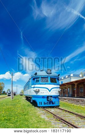 Old vintage locomotive against wonderful clouds and sky by sunny springtime day