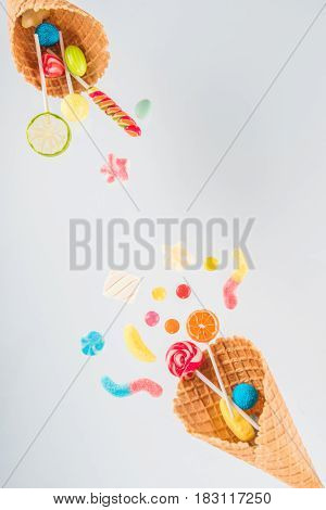 Waffle Cones With Different Delicious Jelly Candies And Lollipops On White