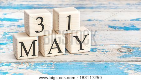 May 31st. Wooden cubes with date of 31 May on old blue wooden background.