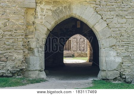Ancient arch doorway leading through passage of medieval castle