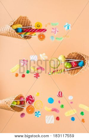 Waffle Cones With Different Delicious Jelly Candies And Lollipops On Beige