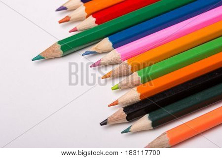 Wooden colorful pencils on a white wooden background
