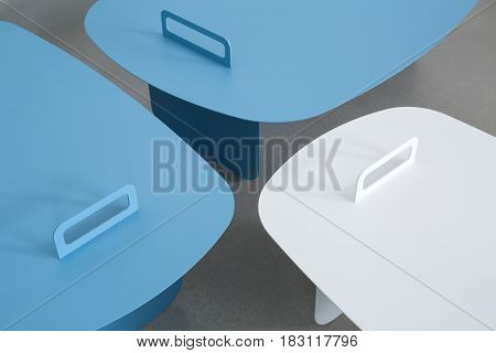 Two cyan and one white metal stands on the gray surface. Closeup photo. Indoors. Horizontal.