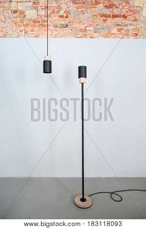 Two black lamps with light wooden parts on the background of the gray and brick walls. One lamp is standing on the floor, second lamp is hanging on the cable. Indoors. Vertical.