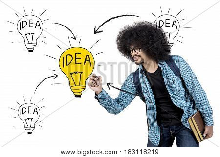 Afro man drawing light bulb on virtual screen while holding book isolated on white background