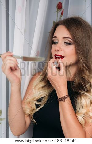 Beautiful girl with red lips and lipstick posing for photographer