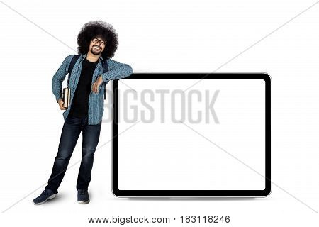 Afro man standing besides copy space on whiteboard while holding book isolated on white background