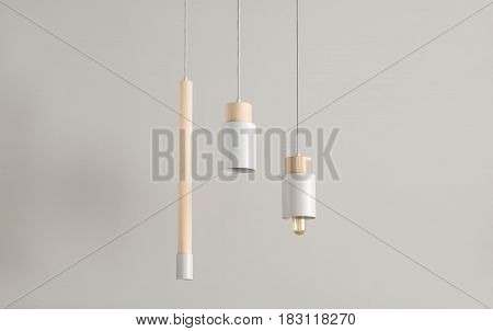 Several gray lamps with light wooden parts are hanging on the cables on the gray wall background. One lamp has an edison bulb. Closeup. Horizontal.