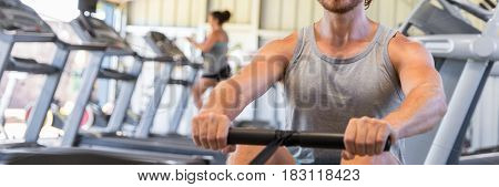 Man athlete training cardio on rowing machine in fitness gym. Closeup of muscular arms pulling resistance equipment. Banner panorama crop.