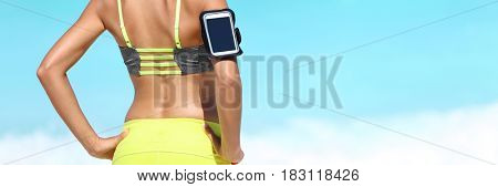 Fitness athlete woman closeup wearing armband for smartphone music listening device. Runner on beach banner crop with copyspace on blue background.
