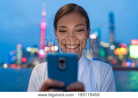 Woman using smart phone at night in Shanghai city, China. Young asian girl texting sms on smartphone app, outdoor urban lifestyle. Tourist chinese businesswoman with cellphone, City lights background