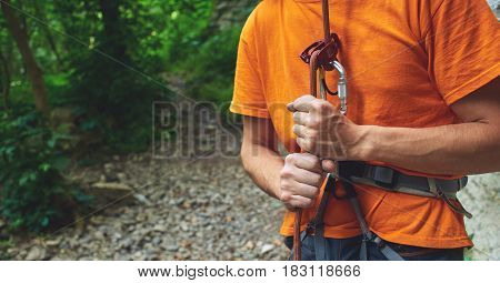 A man insures climber through a belay device. Tubular device on locking carabiner. hands and belay device close up