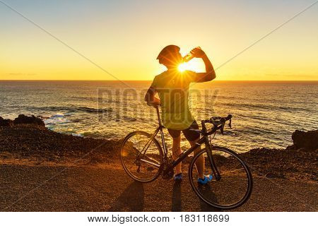Biking Athlete cyclist man drinking water after intensive biking training, enjoying sunset and ocean. Healthy active lifestyle sports fitness man resting on bike with sun flare.